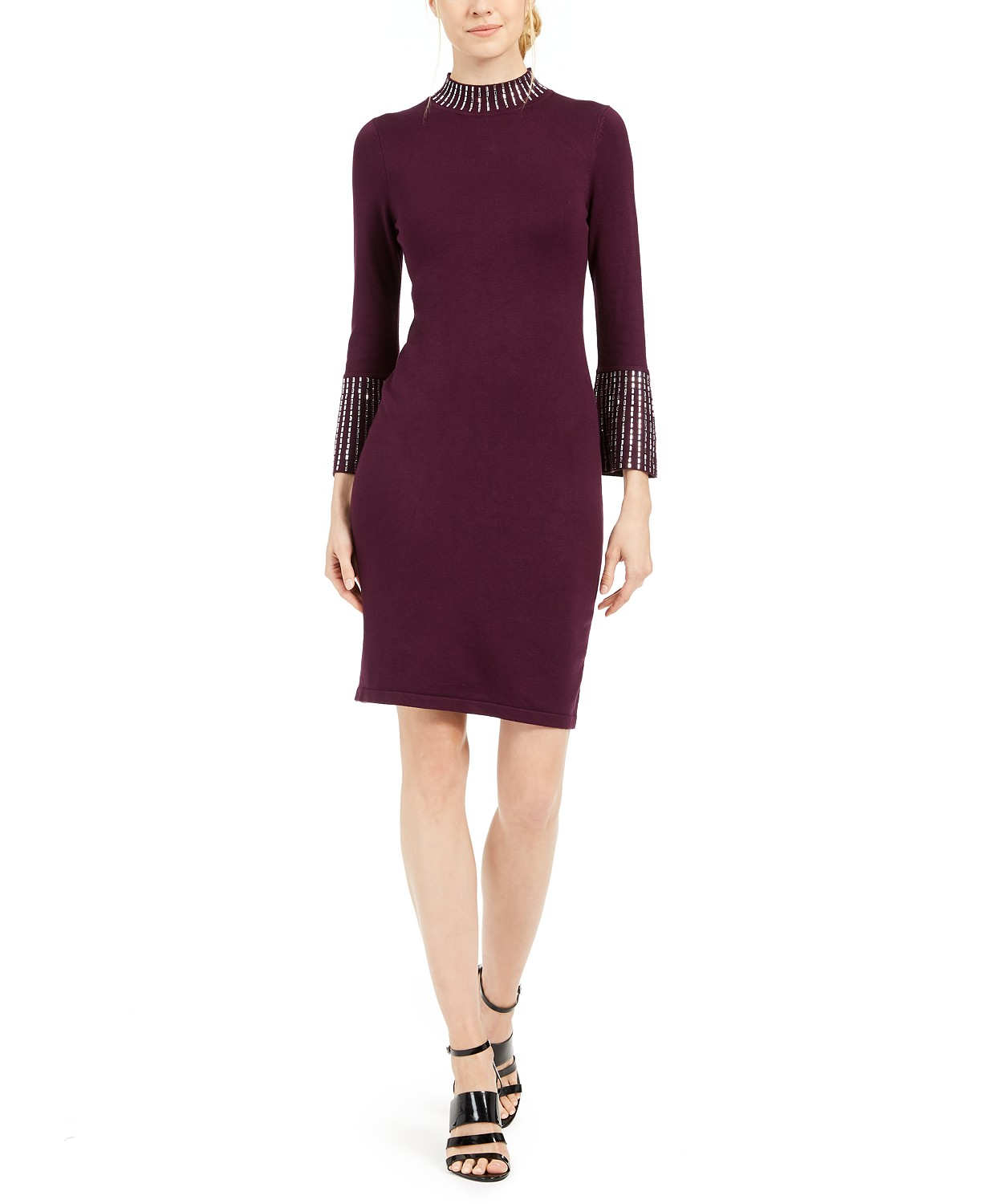 Woman in a burgundy Christmas party dress with white embellishment.