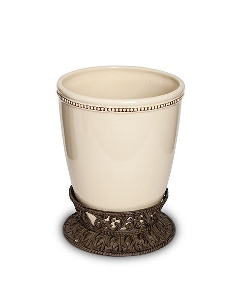 The GG Collection Small Cream Ceramic Wastebasket With Acanthus Leaf Metal Base