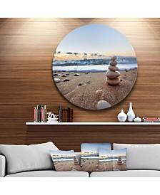 "Designart 'Stones Balance On Sandy Beach' Seashore Metal Circle Wall Art - 23"" x 23"""