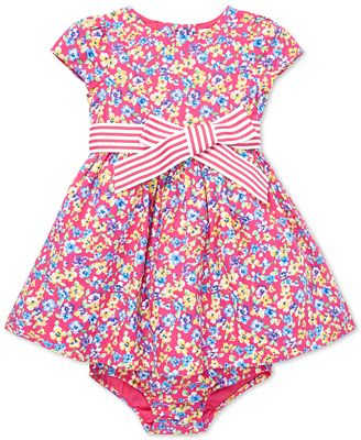 This infant Easter dress for a baby girl has an allover floral print that is beautiful for springtime wear.  It has an exaggerated bow sash at the front with cap sleeves.  Matching bloomers make a complete set for baby.